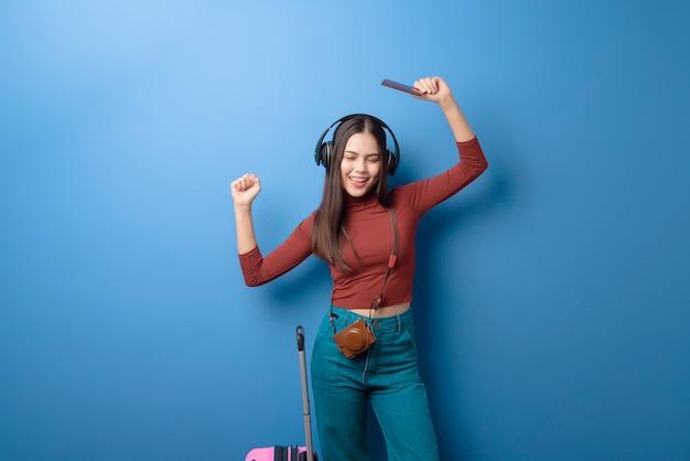 Retrato de uma jovem feliz e bonita ouvindo música e viajando a bordo com passaporte