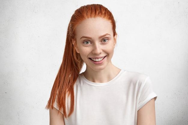 Retrato de uma jovem feliz e satisfeita com cabelo ruivo, vestida com uma camiseta branca casual, tem uma expressão feliz ao descobrir sobre a promoção no trabalho, compartilha o sucesso com os amigos, gosta de seu trabalho.