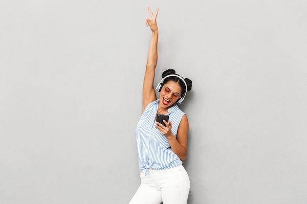 Retrato de uma jovem feliz em óculos de sol, isolado, segurando o telefone celular, ouvindo música com fones de ouvido
