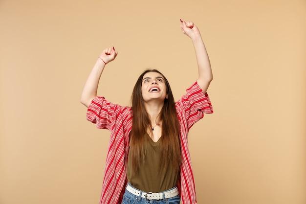 Retrato de uma jovem feliz em roupas casuais, olhando para cima, levantando as mãos, fazendo o gesto vencedor isolado no fundo da parede bege pastel. emoções sinceras de pessoas, conceito de estilo de vida. simule o espaço da cópia.