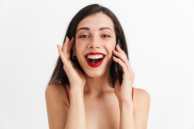 Retrato de uma jovem feliz em um vestido isolado, falando no celular