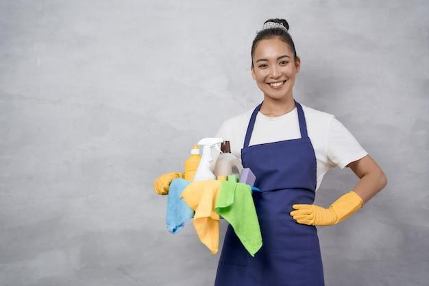 Retrato de uma jovem feliz faxineira de uniforme com balde de material de limpeza