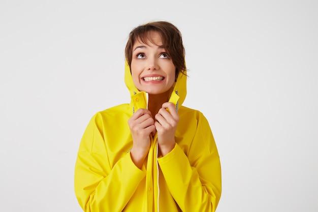 Retrato de uma jovem feliz fofa garota de cabelos curtos usa uma capa de chuva amarela, se escondendo sob uma capa de chuva, amplamente sorri e olha para cima, fica sobre uma parede branca.
