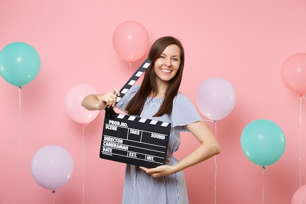 Retrato de uma jovem feliz linda com vestido azul, segurando o clássico filme preto, fazendo claquete sobre fundo rosa com balões de ar coloridos. festa de aniversário, emoções sinceras de pessoas.