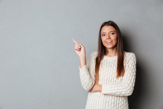 Retrato de uma jovem feliz na camisola, apontando o dedo