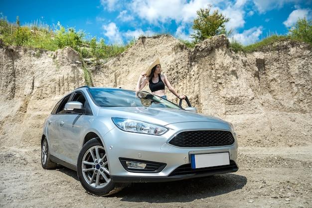 Retrato de uma jovem feliz perto de um carro na areia da praia, horário de verão para relaxar