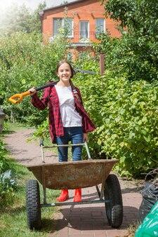 Retrato de uma jovem feliz posando com um carrinho de mão e uma pá no jardim em dia de sol