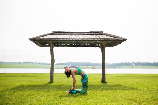 Retrato de uma jovem feliz praticando ioga ao ar livre