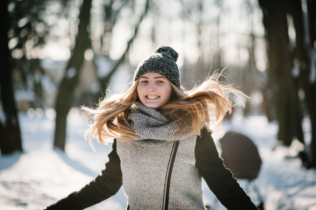 Retrato de uma jovem feliz pulando e curtindo a neve em um parque de inverno.