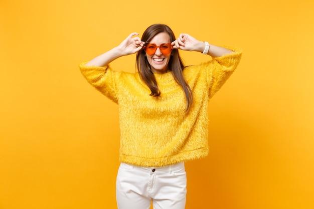 Retrato de uma jovem feliz rindo em um suéter de pele, calças brancas segurando óculos de coração laranja, isolados no fundo amarelo brilhante. emoções sinceras de pessoas, conceito de estilo de vida. área de publicidade.