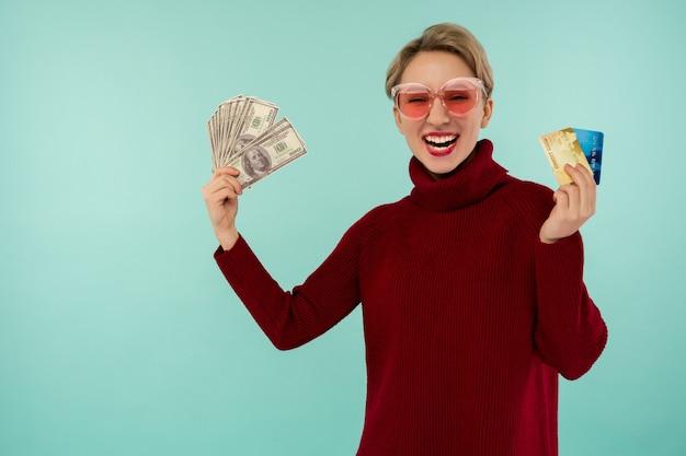 Retrato de uma jovem feliz segurando cartão de crédito e dinheiro sorrindo