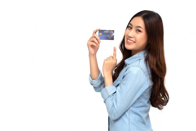 Retrato de uma jovem feliz, segurando o atm ou cartão de débito ou crédito e usando para compras on-line, gastando muito dinheiro isolado sobre a parede branca, modelo feminino asiático