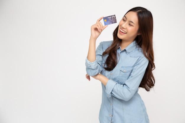 Retrato de uma jovem feliz, segurando o atm ou cartão de débito ou crédito e usando para compras on-line, gastando muito dinheiro isolado sobre a parede branca, modelo feminino asiático Foto Premium