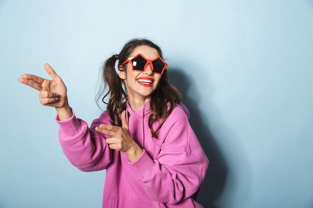 Retrato de uma jovem feliz usando óculos escuros engraçados, rindo e brincando sobre azul no estúdio