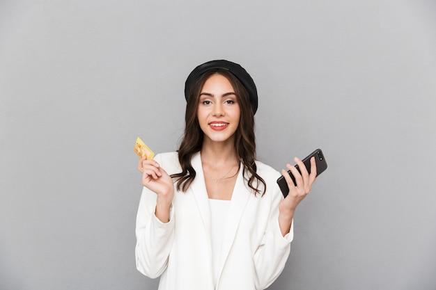 Retrato de uma jovem feliz, vestida com uma jaqueta sobre fundo cinza, segurando o telefone celular, mostrando o cartão de crédito