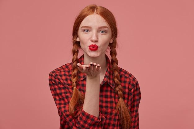 Retrato de uma jovem fêmea de gengibre, com rabo de cavalo e batom vermelho, mostrando um gesto de beijo enquanto flertava com o novo namorado.