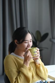 Retrato de uma jovem fofa bebendo café e sorrindo enquanto está sentada no escritório