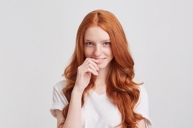 Retrato de uma jovem fofa feliz com cabelo ruivo comprido e ondulado, vestindo camiseta e sentindo-se tímido