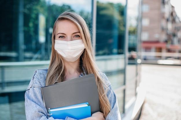 Retrato de uma jovem freelancer usando uma máscara protetora médica