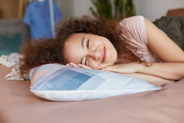 Retrato de uma jovem garota afro-americana alegre deitada na cama, desfrutar da manhã ensolarada em casa, sorrindo e parece feliz.