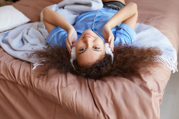 Retrato de uma jovem garota afro-americana encaracolada, deitada na cama com a cabeça baixa, ouvindo música favorita em fones de ouvido, amplamente sorrindo e parece com expressão feliz.