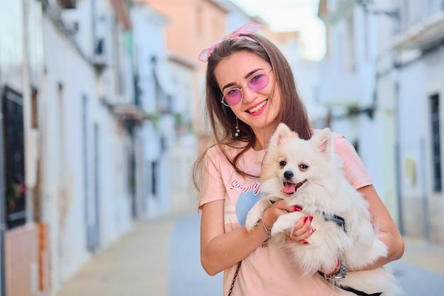 Retrato de uma jovem garota andando com um pomeranian macio branco.