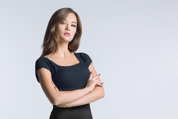 Retrato de uma jovem garota atraente com braços cruzados