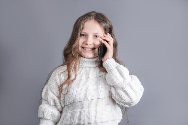 Retrato de uma jovem garota atraente com cabelo comprido e esvoaçante loiro em um suéter branco falando ao telefone