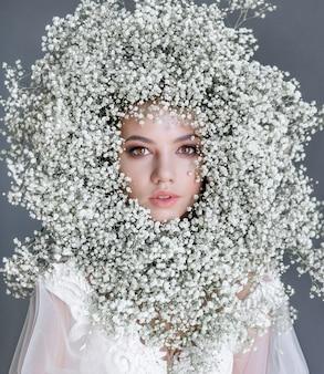 Retrato de uma jovem garota bonita com círculo feito de gypsophila fresca no rosto vestido com blusa branca