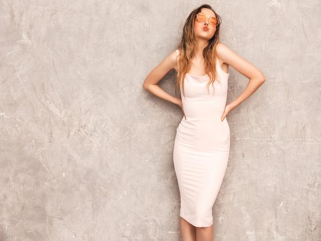 Retrato de uma jovem garota bonita e sorridente na moda verão luz vestido rosa. mulher despreocupada sexy posando. modelo positivo se divertindo e dando beijo
