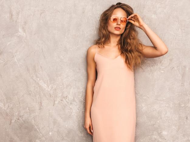 Retrato de uma jovem garota bonita e sorridente na moda verão luz vestido rosa. mulher despreocupada sexy posando. modelo positivo se divertindo em óculos de sol redondos