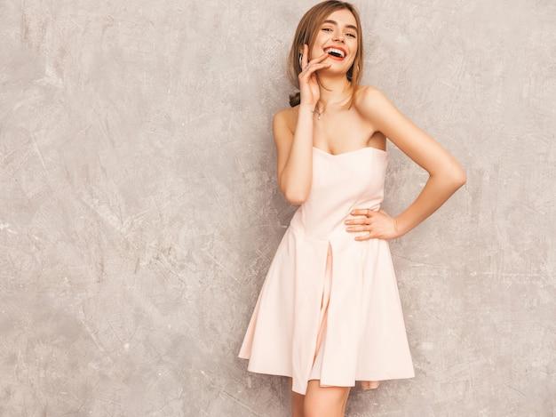 Retrato de uma jovem garota bonita e sorridente na moda verão luz vestido rosa. mulher despreocupada sexy posando. modelo positivo se divertindo