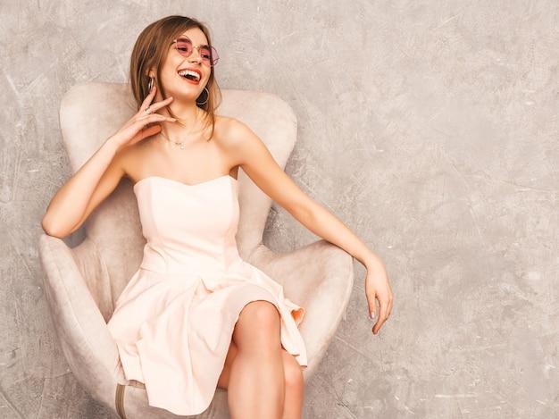 Retrato de uma jovem garota bonita e sorridente na moda verão luz vestido rosa. mulher despreocupada sexy, sentado na cadeira bege. posando no interior de luxo