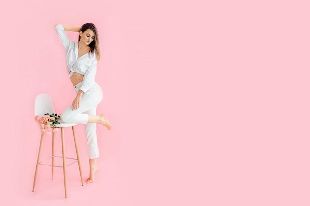 Retrato de uma jovem garota bonita em uma camiseta branca e calça jeans branca, perto de uma cadeira alta branca em que as flores se deitam, olha para o lado, isolado