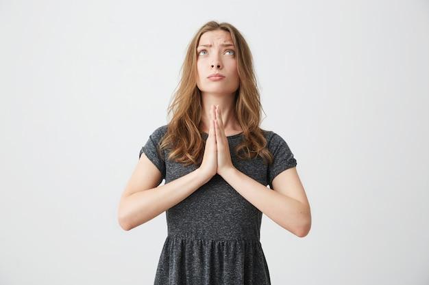 Retrato de uma jovem garota bonita olhando para cima rezando.