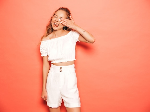 Retrato de uma jovem garota bonita sorridente hipster em roupas da moda no verão. mulher despreocupada sexy posando perto de parede rosa. modelo positivo se divertindo. mostra a língua e cobre o rosto com a mão