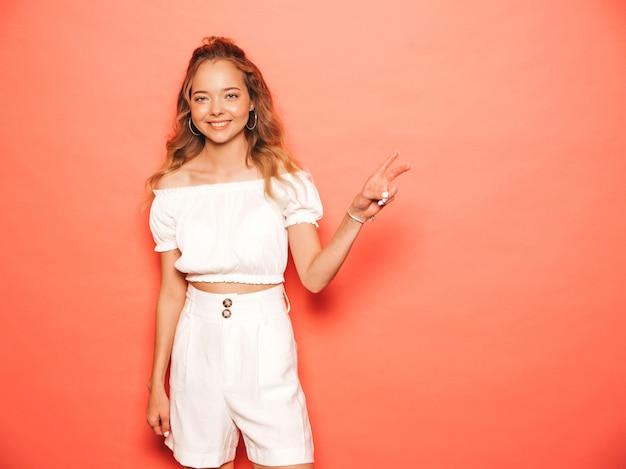 Retrato de uma jovem garota bonita sorridente hipster em roupas da moda no verão. mulher despreocupada sexy posando perto de parede rosa. modelo positivo se divertindo. mostra o sinal de pece