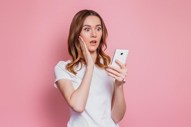 Retrato de uma jovem garota chocada olhando para o telefone e lê mensagens ou notícias isoladas sobre parede rosa. mulher surpreendida em uma camiseta branca com celular