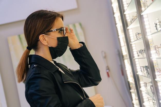 Retrato de uma jovem garota com uma máscara médica que escolhe óculos para si mesma em uma loja de óptica. o conceito de visão deficiente entre os pacientes