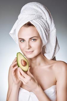 Retrato de uma jovem garota com uma pele saudável e sedosa, com uma toalha branca na cabeça segurando uma fatia de abacate com uma pedra