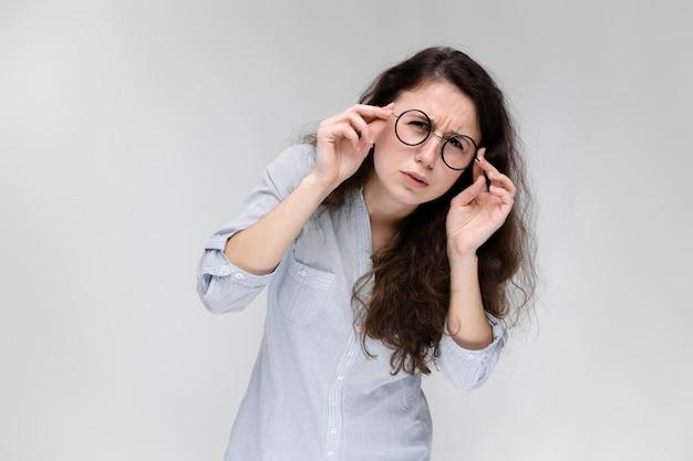 Retrato de uma jovem garota de óculos. linda garota em um fundo cinza.