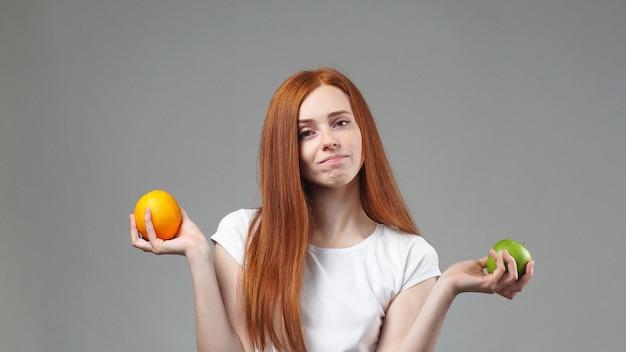 Retrato de uma jovem garota de pé em uma parede cinza perguntou-se que fruta é mais saudável apple ou laranja