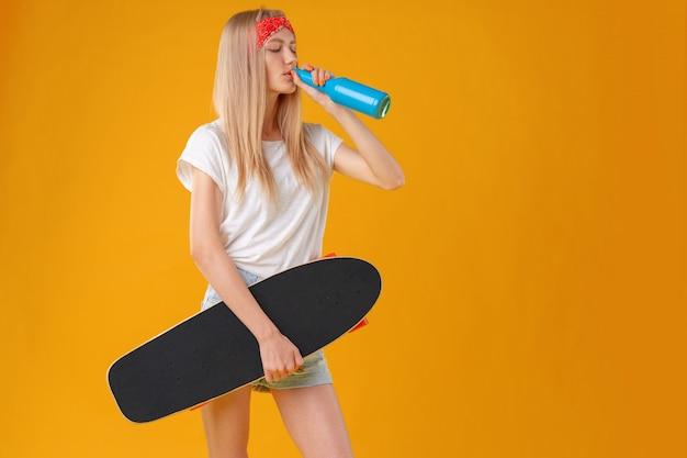 Retrato de uma jovem garota de short curto com longboard