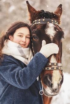Retrato de uma jovem garota e um cavalo no inverno na natureza. fechar-se. vertical