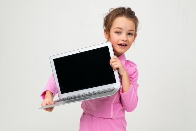 Retrato de uma jovem garota em um terno rosa, mostrando uma tela de laptop