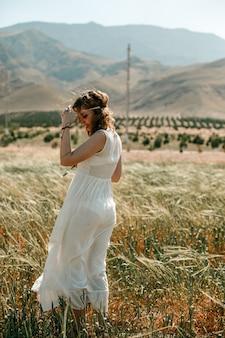 Retrato de uma jovem garota em um vestido branco translúcido no estilo boho ou hippie