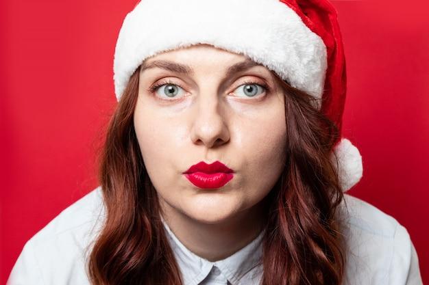Retrato de uma jovem garota encaracolada com um chapéu de papai noel vermelho dá um beijo para a câmera