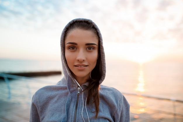 Retrato de uma jovem garota esportiva bonita ao nascer do sol sobre a beira-mar.