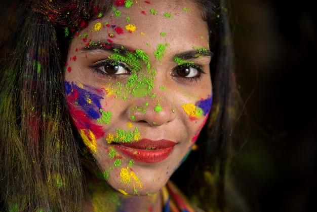 Retrato de uma jovem garota feliz com um rosto colorido por ocasião do festival de holi cor.