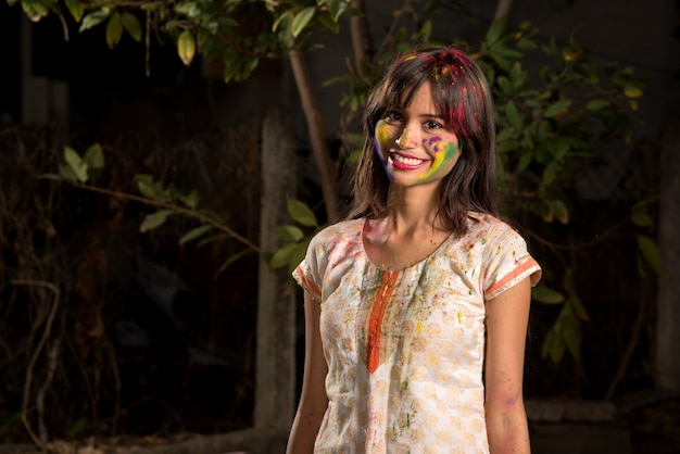 Retrato de uma jovem garota feliz no festival de cores holi. garota posando e comemorando o festival de cores.